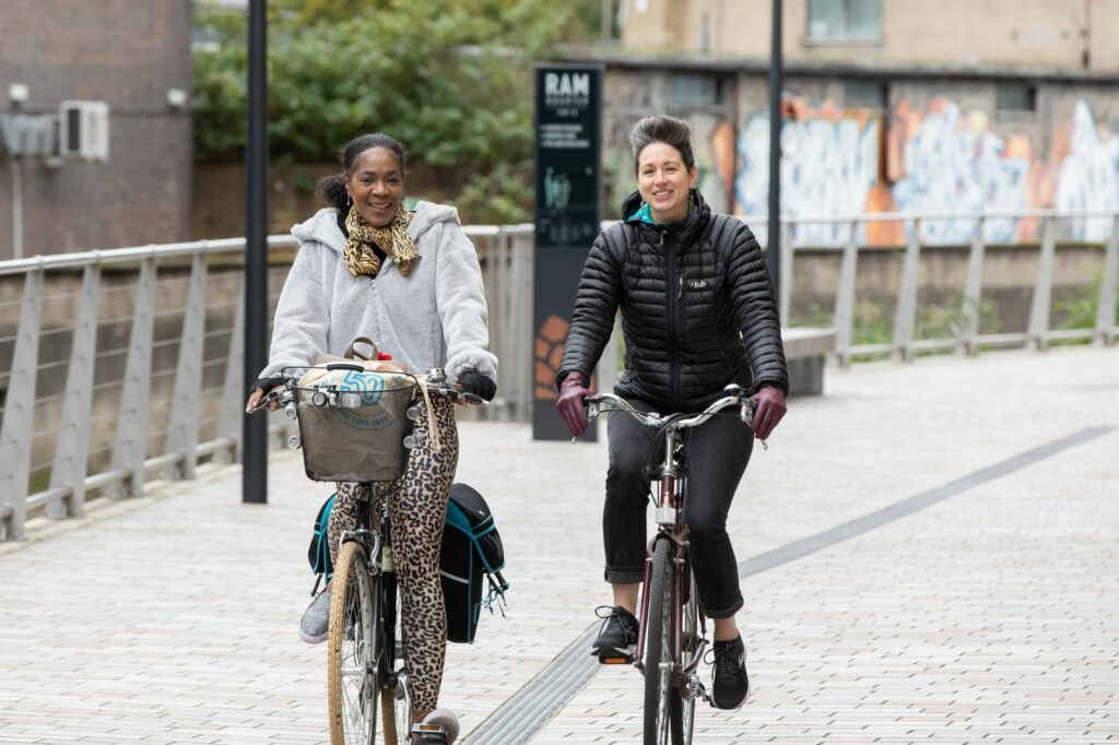 Two women cycle side by side along a quiet street